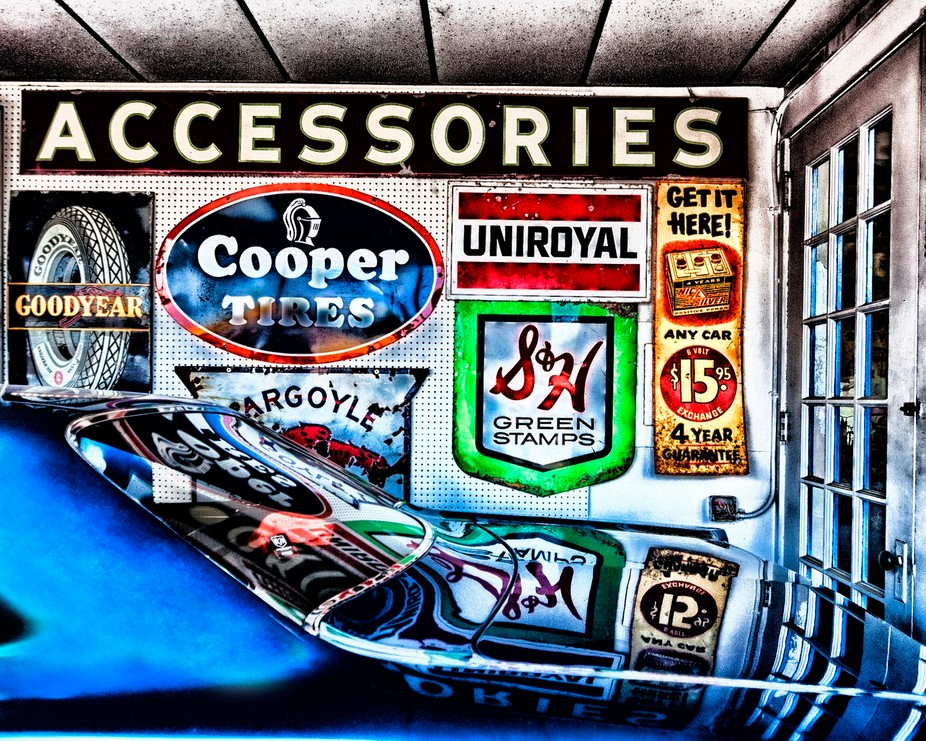 Old signs reflected in the gloss of a vintage automobile...small town showroom...