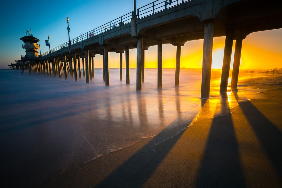 The sun descends behind the pier as the light is dissected into long shadows.