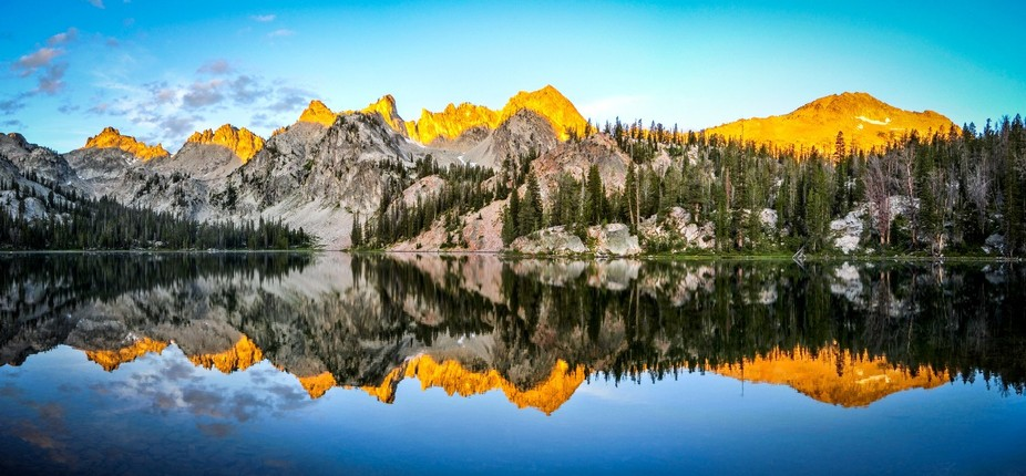 The morning sun touches the tops of the Sawtooth Mountains over Alice Lake in Idaho\'s Sawtooth Wi...