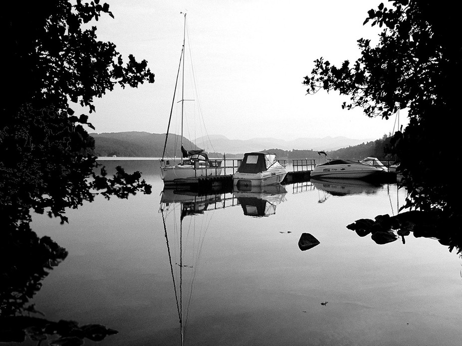 Very Early in the morning Lake Windermere is very still with the mists hanging over the far off h...