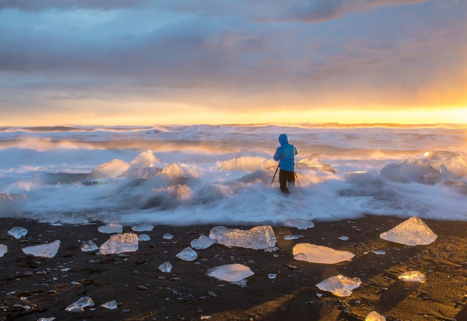 A photographer photographing ice burgs at the Jockusarlon Beach in Iceland at sunrise.