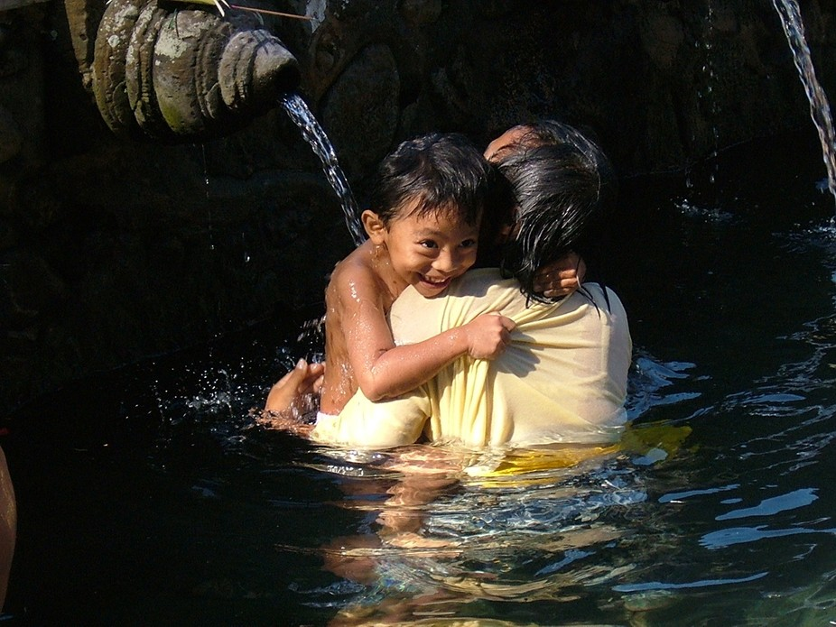 Indonesia child with her mother taking a public bath