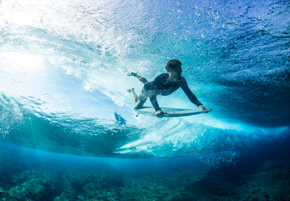 My friend Chris duck diving at cloudbreak while someone else scores a gem of a wave