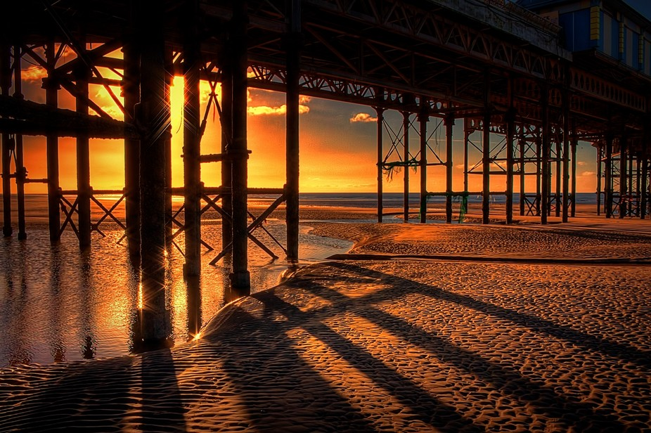 Reflections, flare and shadows under the pier in Blackpool, Lancashire, England.