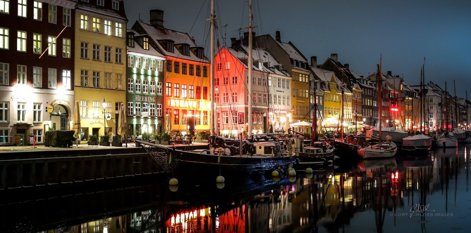 Stark contrast of the colorful, waterfront homes of Nyhavn street in Copenhagen, against the dark...