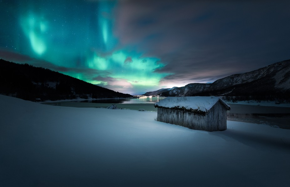 The northern lights provide the perfect backdrop for the beautiful shacks throughout the Norwegia...
