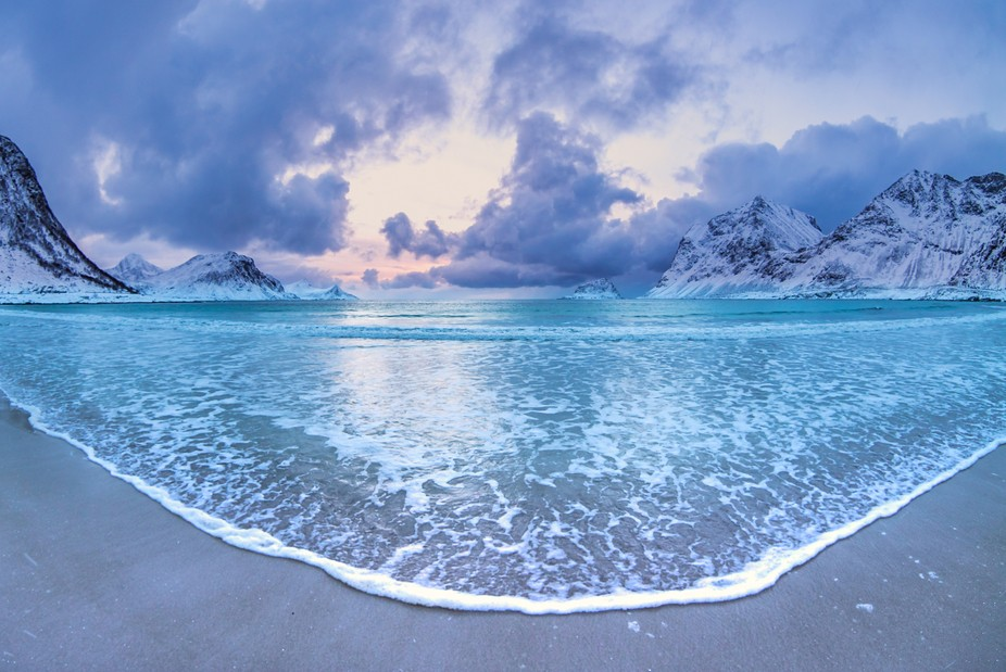 A stunning evening glow settles over a calm evening at Haukland Beach in Lofoten.