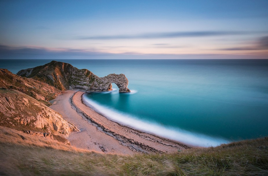 Durdle Door is a natural limestone arch on the Jurassic Coast near Lulworth in Dorset, England. I...
