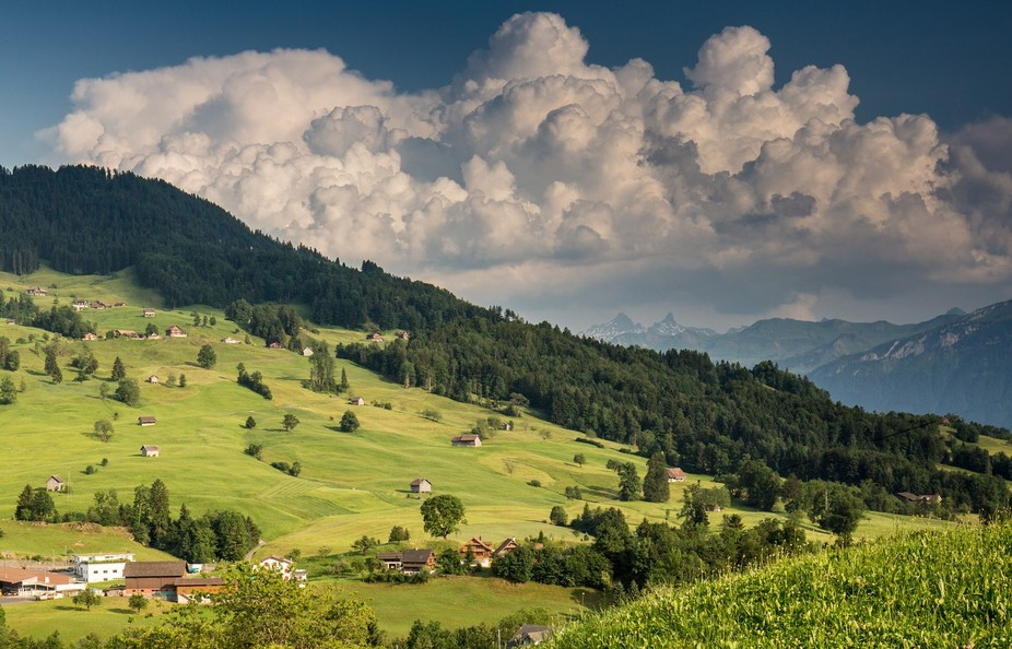 A typical Swiss landscape with stunning clouds on top of the mountains
