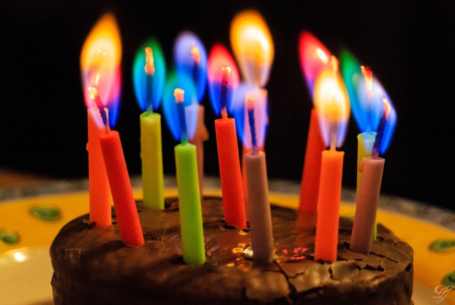 Colorful candles and flames on a birthday cake