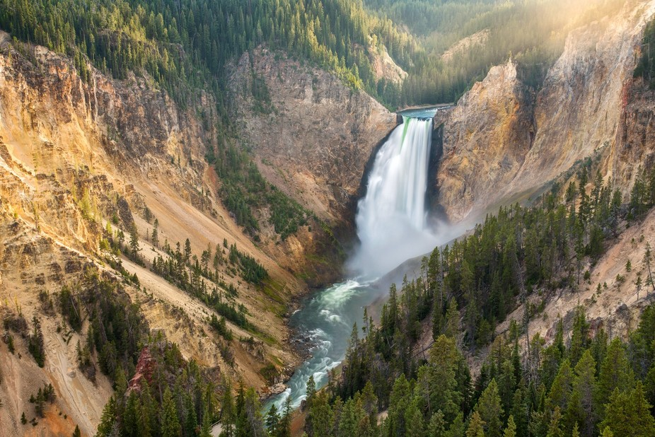 the sun was setting casting its golden light onto the canyon wall. the spray from the powerful fa...