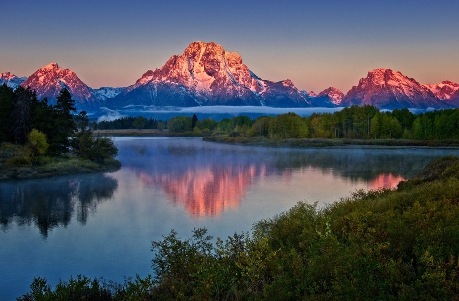 (HDR - 3 exposures)  The upper portion of Mt. Moran lit by the rising sun and reflected in the Sn...