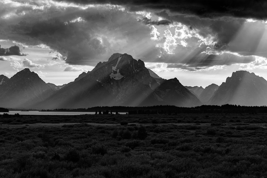 the clouds rolled back just enough to show the sun beaming down on the Tetons of Wyoming