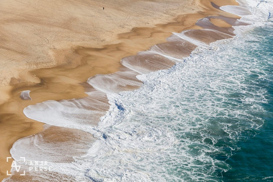 Shot of the ocean reaching a sandy beach. A man is walking down the beach and you can feel how we...