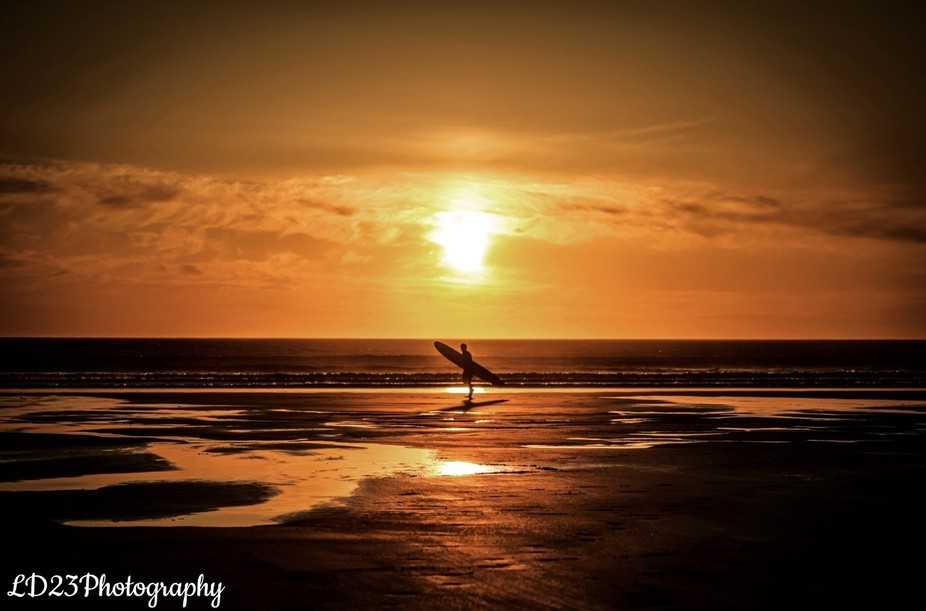 A surfer finishes up his day at Perranporth beach, Cornwall