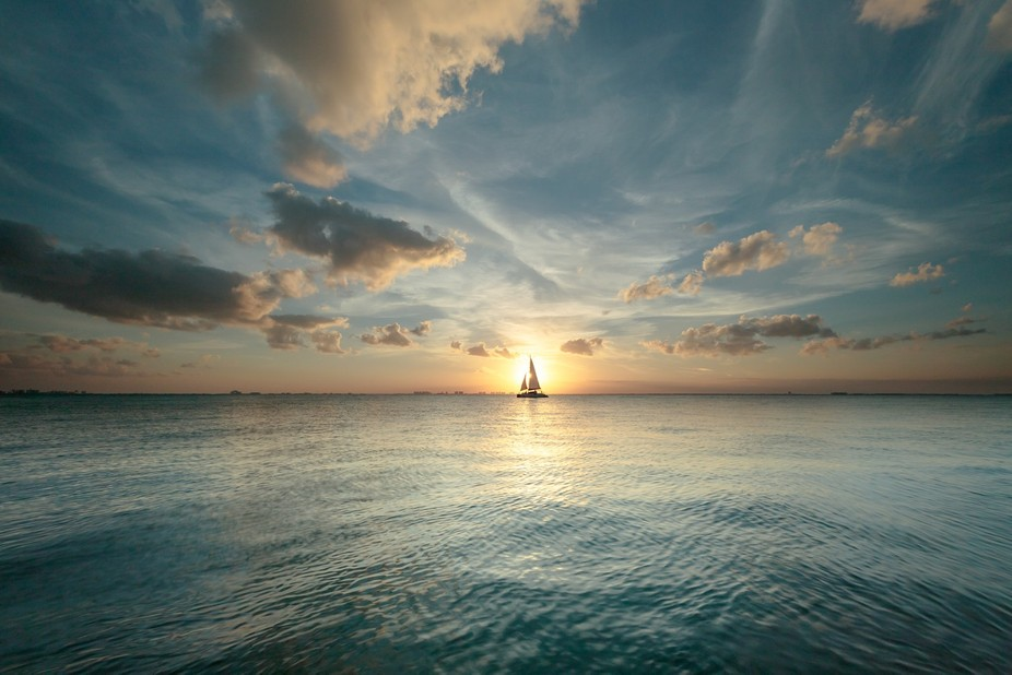 A sailboat crosses in front of the setting sun over Cancun, Mexico. Taken at Maria's Kan...